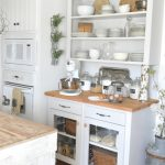 simple white kitchen cabinet design in antique style with open racks and trasnparent glass storage with beige countertop and simple greenery and island