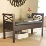 simple wood bench with black leather seating as mudroom furniture a box as books storage mini black pot and ornamental flower  brown basket rug for entrance area