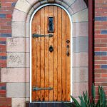 single front door design with natural wood material and cool frame plus brick walls and plants