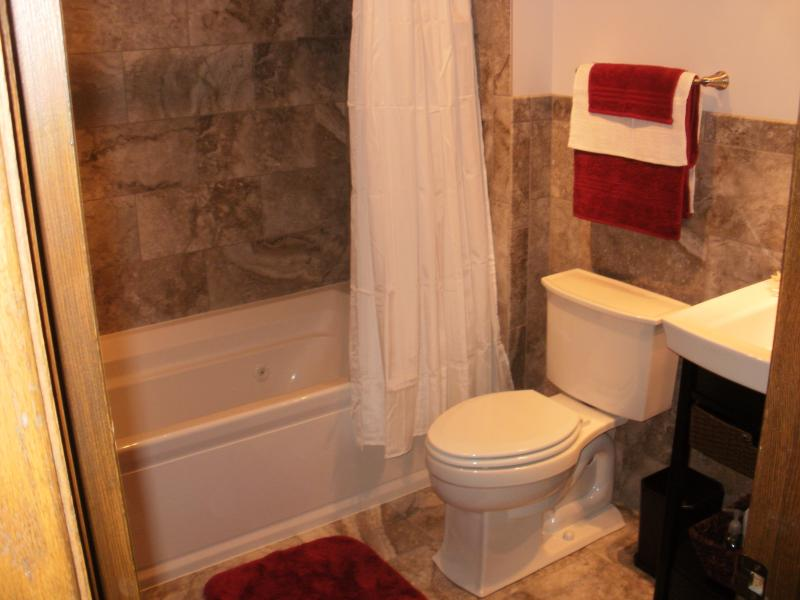 small bath remodel with bathtub and white bathroom curtain and toilet