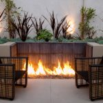 stunning backyard living space with double black rattan lawn chairs design and in ground fire pit idea with small garden