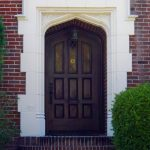 stunning front door design with wood panel and elegant frame combined with lantern lamp and brick wall plus plant