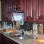 stunning reddish wooden kitchen cabinetry idea with small cases and white marble countertop and round sink and diamond patterned tile antique mirror backsplash