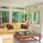 sunroom corner with comfortable sunroom furniture in light yellow plus decorative pillows a glass table top
