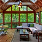 sunroom with a pair of green chairs plus round wood table a L shape sofa with white mattress a side table and regular wood table wood planks flooring a ceiling fan fixture with lamp