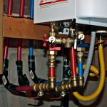tankless water heater installation in wall with wires and pipes and woods