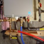 tankless water heater installation with metal pipes and invervals and plumbing and wooden