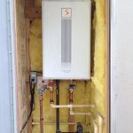 tankless water heater installation with pipes and wires and remote control and sponge