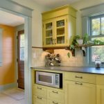three layers crown molding for kitchen a kitchen set in yellow theme under storage system in yellow glass door cabinets on top of kitchen counter