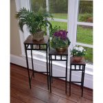 three levels table for indoor plant shelves with wooden counter-top and black metal legs with various pots size and color and greenery beneath glass window with white frame upon wooden floor