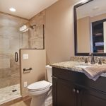 tiny basement bathroom ideas with walk in shower and toilet plus vanity units with granite countertop and sink plus mirror and wall scones
