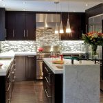 tiny kitchen remodel with dark wooden cabinets and island with marble countertop and sink and stylish backsplash and pendant lamps ang glass table