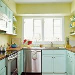 tiny kitchen remodel with turqouise kitchen cabinets and wooden countertops and wall mounted leaves on yellow wall plus wooden laminating floor