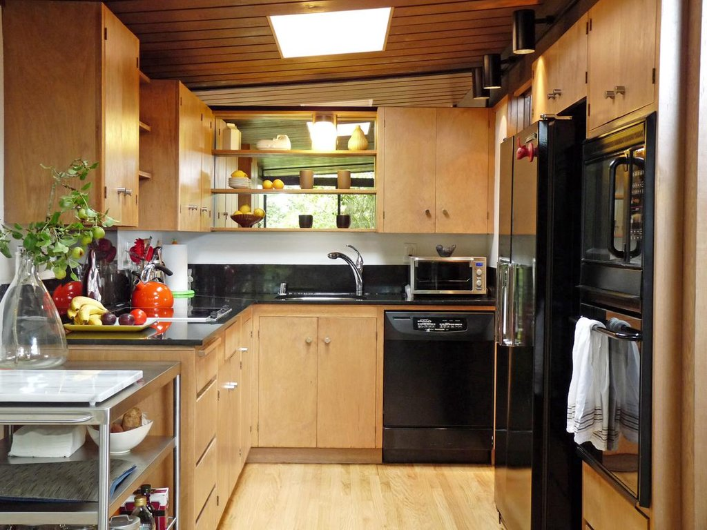 tiny kitchen remodel with wooden cabinets and black countertop with sink and steel kitchen appliances plus wooden laminating floor