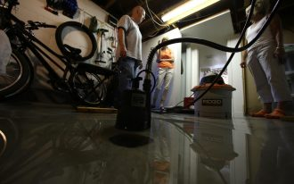 TORONTO, ON -JULY 10 -  Ross Marsden pumps the basement of his son's home. They are lucky to have power but the water won't go away.Royal York and Bloor area of the city has been without regular power since the storm and flood on Monday.  .Toronto, July 10, 2013.         Rene Johnston/Toronto Star