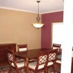 traditional padded chairs on patterned area rug mixed with simple glossy table underlight fixture for delightful dining room with snazzy two tones interior painting style