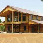 traditional pole barn house with wood material and large glass windows and wood front door