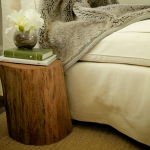 tree stump side table in bedroom with two books and a glass pot plus vivid flower decoration
