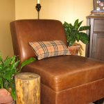 tree trunk stump side table a brown leather corner table with mini pillow a standing lamp behind the chair two decorative plants