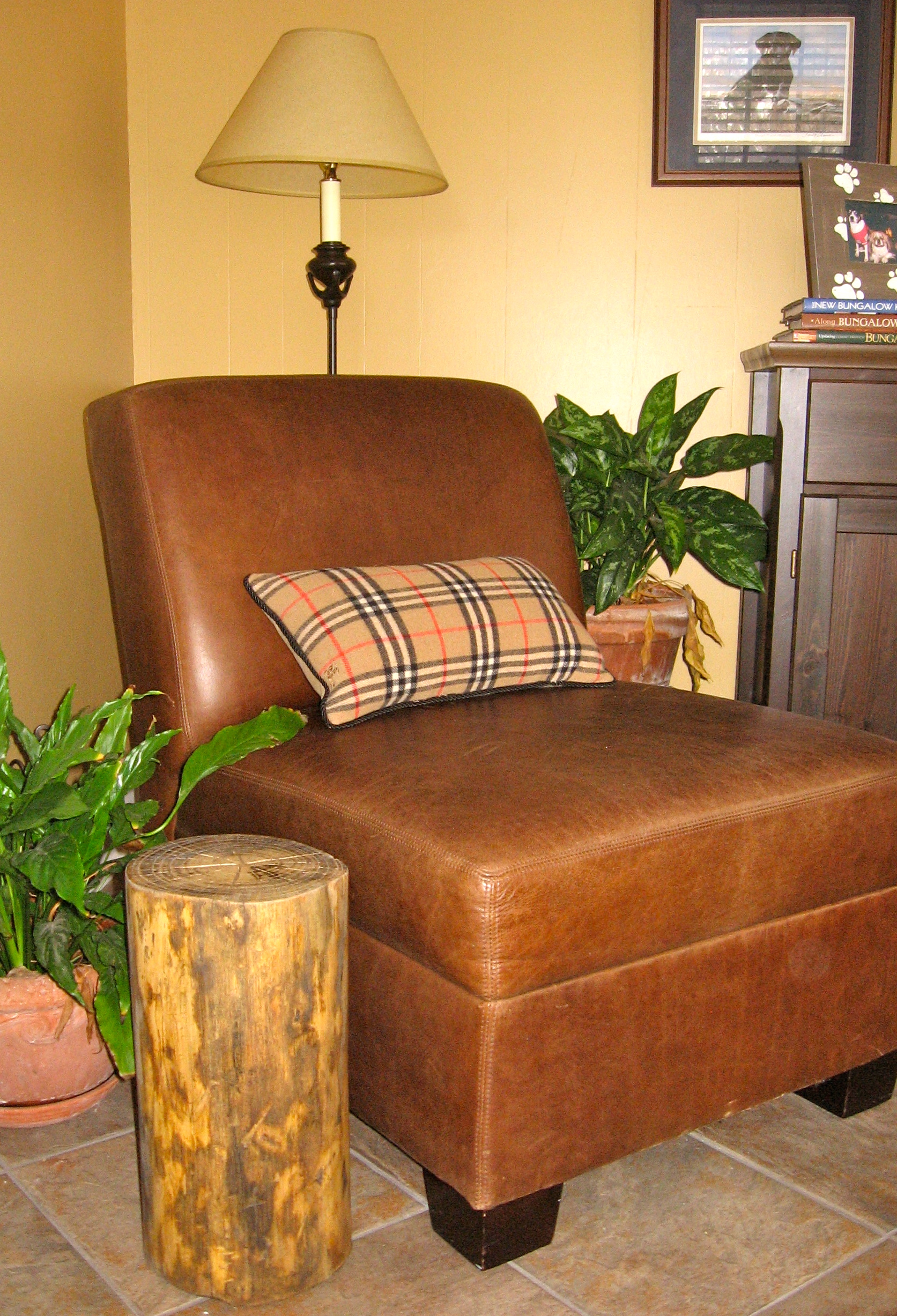 tree trunk stump side table a brown leather corner table with mini pillow a standing lamp