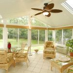 tropical sunroom with rattan furniture plus round glass table top a pair of chairs with square glass table top a fired clay pot with ornamental plant white ceramic floors a ceiling fan with lamp