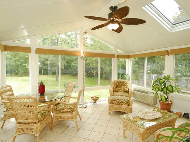 tropical sunroom with rattan furniture plus round glass table top a