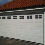two car garage door with windows on top plus brick wall