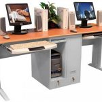 two person computer desk with opened under shelf for CPU and under sliding panel for keyboards two units of monitor two pairs of audio systems a pot with decorative plant