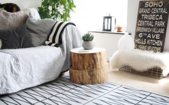 two piles of wood stump side table in natural tone color a small white porcelain pot for small decorative plant modern patterns rug for floors a cozy sofa
