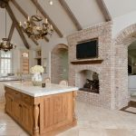 two sided traditional fireplace in rustic style a large kitchen room with traditional pendant light fixtures a kitchen island with the chairs white porcelain tiles for floor