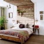 unique bedroom design wit rustic appeal of decorative headboard from vintage wooden board with greenery and ball accessories upon wooden bedding with floral quilt aside small wooden side table