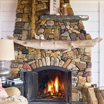 unique concept of fireplace construction with driftwood mantle and colorful river stones wall system