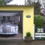 unique garage door with 3d car picture plus yellow wall paint and fences combined with garden