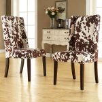 white and black patterns cowhide chairs with dark stained wood legs a classic console table with flower and vase decoration  light wood  color floors