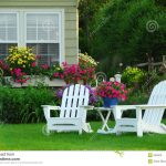 white and short wooden lawn chair design with deck wooden backrest and seating iwth armrests and white table surrounded by lush vegetation upon grassy meadow aside colorful flowers