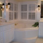 white bathrooms remodeling  with exclusive bath tub and double vanity units with sink and mirrors plus wall scones and windows