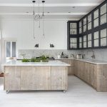 white washed wood floors fr kitchen white surface marble for kitchen island white marble countertop gold faucet  large top cabinetry with transparent glass door and handles three pendant lamps