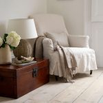 whitewashed wood planks floor system for reading corner a comfy white corner chair with white blanket and pillow a wood case as the side table a classic table lamp a decorative pot and flower