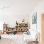 whitewashed wood planks floors for home library medium size book racks  a white simple sofa with wheels as the reading chair an abstrack painting