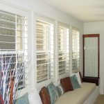 window shutter in white color a long bench under the windows with light cream mattress and multiple colored pillows