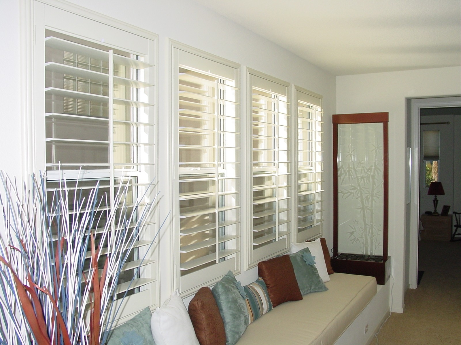 window shutter in white color a long bench under the windows with light cream mattress and - Plantation Shutters Cost