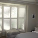 window shutters installation for small bedroom a settee furniture with stripes patterns white bedside furniture a bed furniture a picture frame installed in the wall
