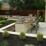 wonderful white outdoor kitchen set facing beautiful landscape seattle design with black pebble field and shrub for garden