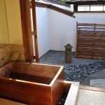 wood Japanese soaking tub in semi outdoor bathroom natural river stones  floors