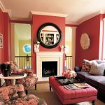 wood crown molding connecting white ceiling and red wall system a set of living room furniture in different designs and colors a modern fireplace a round ornamental mirror