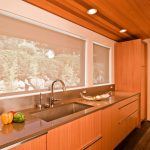 wood kitchen cabinetry with shiny metal handles large and deep sink and shiny metal double faucets hardwood kitchen floor