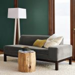 wood stump table and dark grey sofa with yellow and white decorative pillows pure white standing lamp soft white carpet