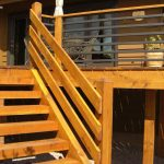 Yellowish Wooden Porch Design With Wooden Staircase And Horizontal Wooden Deck Railing With Black Metal Combination Of Upper Floor