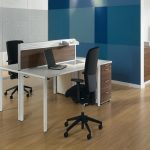 2 person wooden desk ikea with file drawers and modern black swift chairs combined with wooden laminate floors and blue wall scheme and notebook