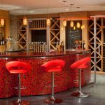 Attractive wine bar for private house with bright red bar chairs and red black mosaic bar table wall a large wine storage made from wood material